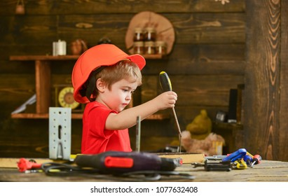 Handcrafting and workshop concept. Child in helmet cute playing as builder or repairer, or handcrafting. Toddler on busy face plays with screwdriver at workshop. Kid boy holds screwdriver tool.