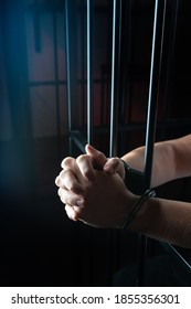 Handcuff on man's arms, praying for forgiveness in Church. prisoner in handcuffs praying, prisoner prays in a cell behind bars