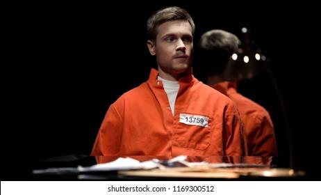 Handcuffed maniac in orange prison jumpsuit looking around in interrogation room