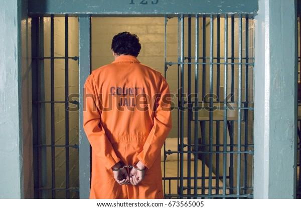Więzień skuty kajdankami w więzieniu