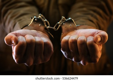 Handcuffed soldier, arrested male army officer in dark prison cell