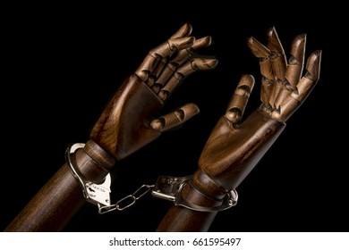 Handcuffs attach two black hands together. With copy space text. Isolated on black background. Studio Shot.
