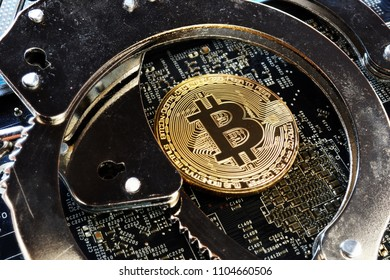 Handcuffs and Bitcoin coin. Crime with cryptocurrency.