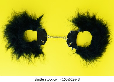 Handcuffs with black hair sex toy for adult, design minimal isolated on yellow background