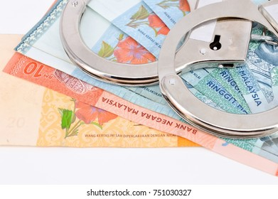 Handcuffs closeup on malaysia banknote.Corruption problem in the world.
