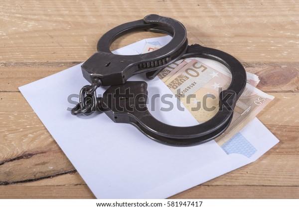 Handcuffs and euro bills