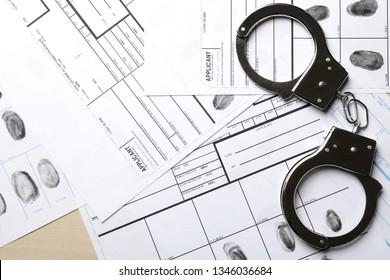Handcuffs and fingerprint record sheets, top view. Criminal investigation