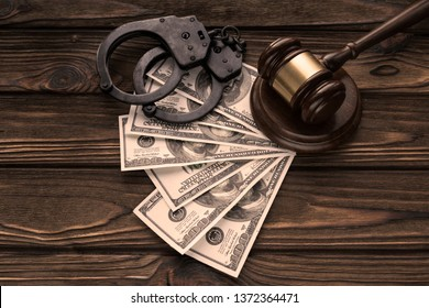 Handcuffs, gavel, judge, banknotes of American dollars on the background of wooden table. arrest, crime, embezzlement.