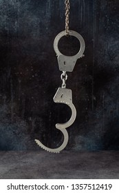 Handcuffs hanging against a grunge dark background