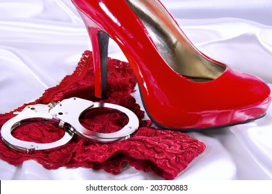 Handcuffs and high heel close up, on white background.
