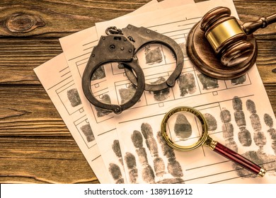 Handcuffs, the judge's gavel, magnifying glass, finger prints on the background of wooden table.criminal. arrest. prison, misdemeanor.