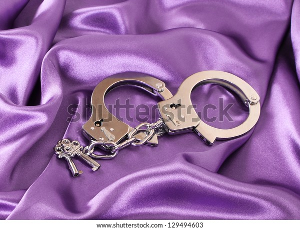 handcuffs and keys on purple silk fabric