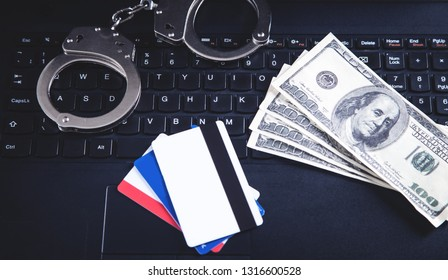 Handcuffs, money, credit cards on computer keyboard. Concept of  Cyber crime and Online fraud