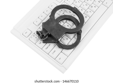Handcuffs on computer keyboard isolated on white