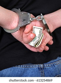 Handcuffs on the Hands with a Money Closeup