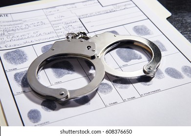Handcuffs on top of a set of fingerprints file