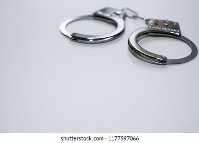 Handcuffs on a white background in the upper left corner of the frame. The concept of violation of the law in the financial sphere, fraud, corruption, bribery. Copy space.