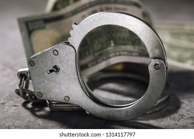 Handcuffs and one hundred dollar bill on the table. Concept on the topic of fraudulent transactions with money entails punishment