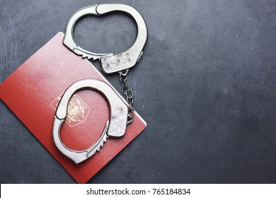 Handcuffs and passport on dark background suggesting illegal immigration problem