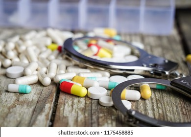 Handcuffs and pills and drugs on wooden table. Selective focus