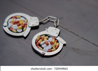 Handcuffs and pills. Selective focus