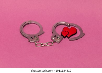 Handcuffs with red love hearts on a pink background. End of bachelorhood. With copy space to add text.