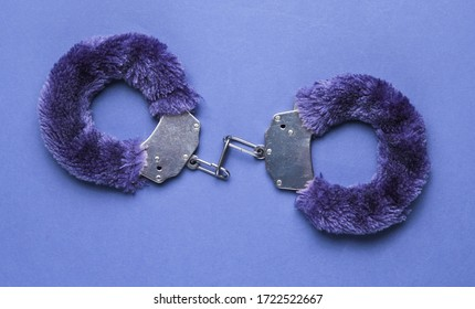 Handcuffs for sex games on blue background. Sexual bdsm toy. Fetish, erotic concept.