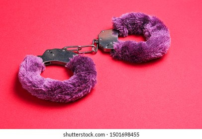 Handcuffs for sex games on red background. Sexual bdsm toy. Fetish, erotic concept.