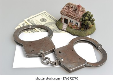Handcuffs, toy house and white envelope with money on gray background
