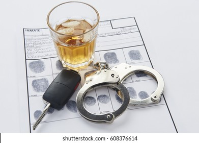 Handcuffs, whiskey, and keys on top of finger prints