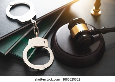Handcuffs and wooden gavel. Crime and violence concept.
