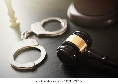 Handschellen und hölzernes Tuch. Konzept von Kriminalität und Gewalt.