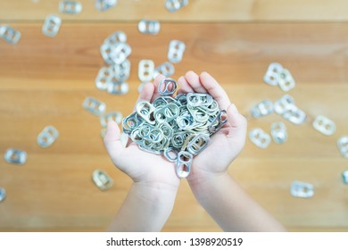 Handful of aluminum pull tabs in kid's hand with other pull tabs spread around on wooden table in background. Waste separation, sorting, recycle concept. Material for prosthetics.