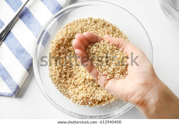 Handful of brown rice taken from glass bowl