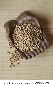A handful of chickpeas in a wooden bowl on the kitchen table.