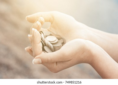Handful of coins in palm female hands. Concept of saving and passive income. Instagram beige toned