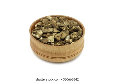 a handful of dried burdock root in a wooden bowl on a white background