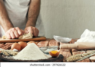 A handful of flour with egg on a rustic kitchen. Against the background of men's hands knead the dough. Ingredients for cooking flour products or dough (bread, muffins, pie, pizza dough). Copy space