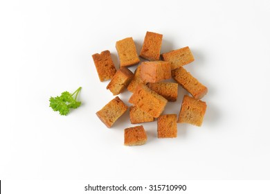 handful of fried bread cubes (croutons) on white background