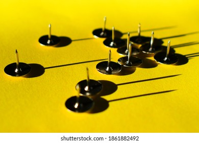 A handful of gold thumbtacks on a bright yellow background
