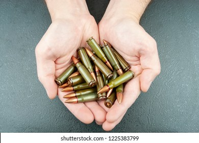 Handful of green 7.62 mm cartridges for Kalashnikov assault rifle in man's hands. Top view