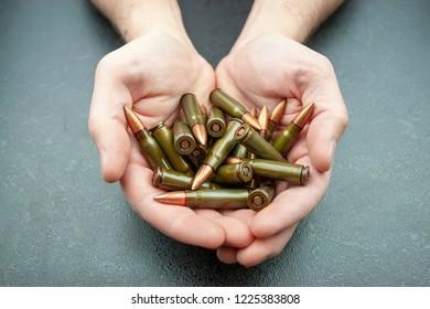 Handful of green 7.62 mm cartridges for Kalashnikov assault rifle in man's hands