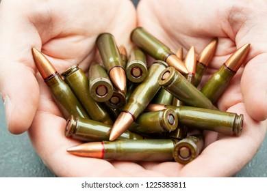 Handful of green 7.62 mm cartridges for Kalashnikov assault rifle in man's hands. Closeup