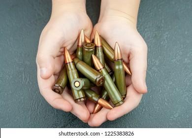 Handful of green 7.62 mm cartridges for Kalashnikov assault rifle in children's hands