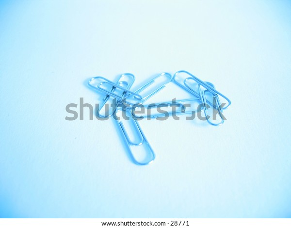 A handful of metal paperclips in blue light.