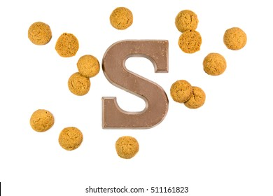 Handful of Pepernoten cookies or ginger nuts with chocolate letter as Sinterklaas decoration on white background for dutch sinterklaasfeest holiday event on december 5th