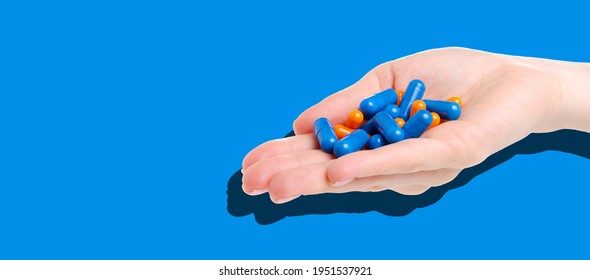 handful pills capsules in hand on blue background, copy space