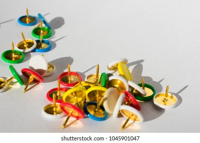 A handful of pushpins in a random position on a white background.