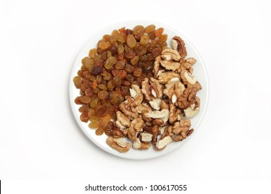A handful of raisins and shelled nuts on the white plate