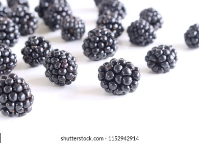 Handful of ripe scattered blackberries isolated on white table. Delicious fruit . Blurred background.Food and healthy concept.